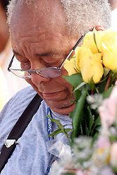 29 August 2006. Lower 9th Ward. New Orleans, Louisiana. <br /> Henry Irvin Snr, former resident of the Lower 9th ward hangs his head in a moment of silence and reflection at the Great Flood commemoration and memorial ceremony; to 'honor and remember our loved ones who have passed. The one year anniversary of hurricane Katrina.<br /> Photo credit©; Charlie Varley/varleypix.com