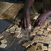 A woman making manioc biscuits by hand at Biscuiterie H. Rault, a family-owned factory in Mahebourg, Mauritius that has been making the biscuits in the same way for over 140 years. Visitors can tour the factory and sample the biscuits in the garden with tea.