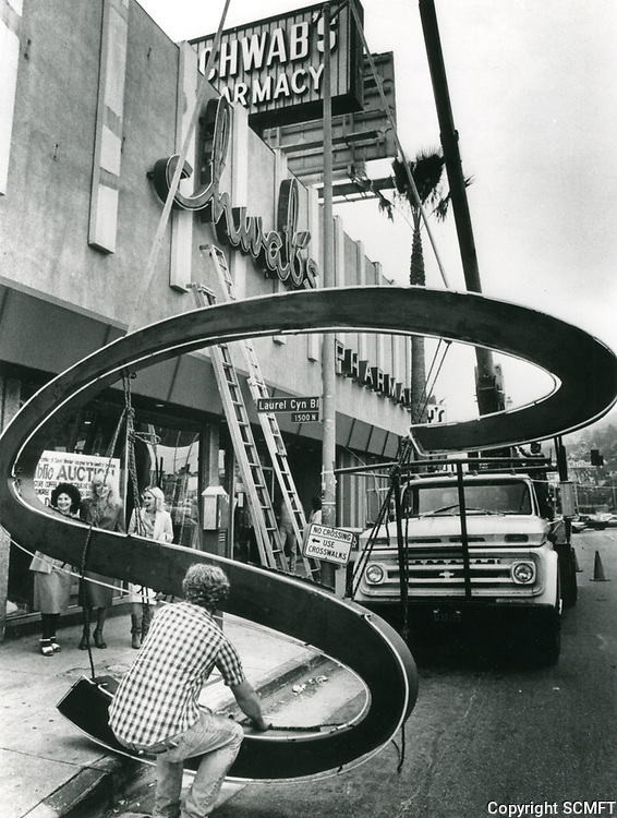 """1983 Removing the letter """"S"""" from the sign during demolition of Schwab's Drug Store"""