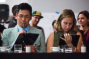 Judges Chris Gaoiran of Bellano Coffee in Santa Clara, left, and Annie McGee of Verve Coffee Roasters in Santa Cruz makes notes on drinks prepared by Justin Williams, 25, of Front Café in San Francisco during the 2nd Annual Mock Barista Competition and Brewer's Cup at San Pedro Square Market in San Jose, California, on February 21, 2013.  (Stan Olszewski/SOSKIphoto)