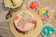 Decorating a birthday cake with icing sugar ballet shoes,