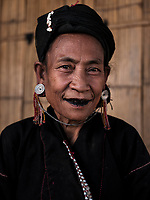 KYAING TONG, MYANMAR - CIRCA DECEMBER 2017: Portrait of a woman at the Bam Kin Mai Eng. The Eng tribe are known for their black teeth. They believe black teeth are attractive and chew tree bark and beetle nut to darken them.<br /> Kyaing Tong