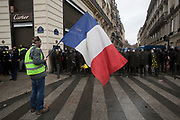 December, 8th, 2018 - Paris, Ile-de-France, France: Demonstrator holding French national flag on Champs Elysees. The French 'Gilets Jaunes' demonstrate a fourth day. Their movement was born against French President Macron's high fuel increases. They have been joined en mass by students and trade unionists unhappy with Macron's policies. Nigel Dickinson