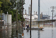 Worker dumping soda ash in contaminated floodwater next to the Honeywell chemical plant in Geismar, Louisiana following the 1000-year flood.