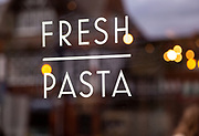 Fresh pasta sign in glass window of Italian restaurant blurred background some reflection, UK