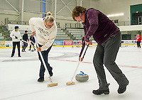 "Kim Conrad and Lori McGinley are on sweep for the ""Broom Broom Pow"" team during Curling League play at the Plymouth State University Ice Arena Thursday evening.   (Karen Bobotas/for the Laconia Daily Sun)"