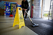 A female wing cleaner hoovers the matt at the  entrance to a wing at HMP Bronzefield, a private prison run by Sodexo Justice Services on the outskirts of Ashford in Middlesex, United Kingdom. HMP Bronzefield is an adult and young offender female prison, the only purpose built private prison solely for women in the UK and is the largest female prison in Europe. (photo by Andy Aitchison)