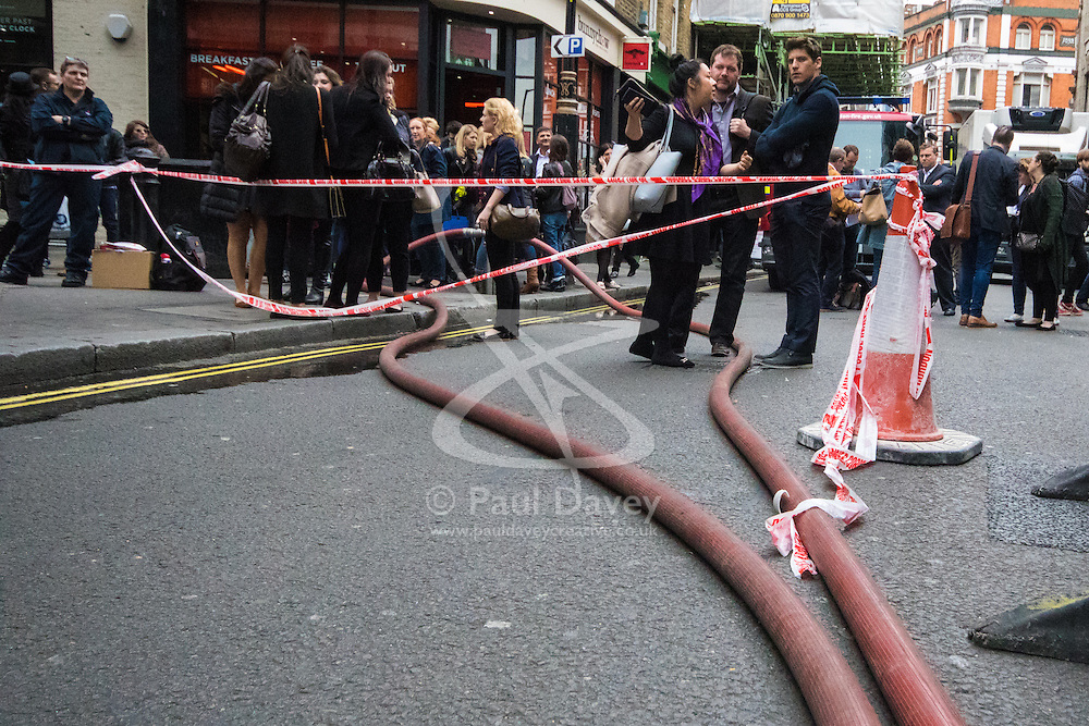 Soho, London, May 8th 2015. Firefighters deal with a fire that broke out at lunchtime in the kitchens of Carom and Floridita, a pair of Wardour Street restaurants in the heart of Soho. The cause is still being investigated. PICTURED: Office workers wait outside the police cordojn, unable to return to work.