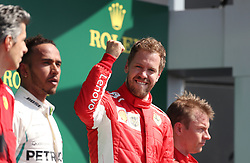 Ferrari's Sebastian Vettel (centre) celebrates victory on the podium, with Mercedes' Lewis Hamilton (left) and Ferrari's Kimi Raikkonen (right) during the 2018 British Grand Prix at Silverstone Circuit, Towcester.