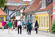 Visitors strolling in Ramsherred cobbled street in old town in Odense on Funen Island, Denmark