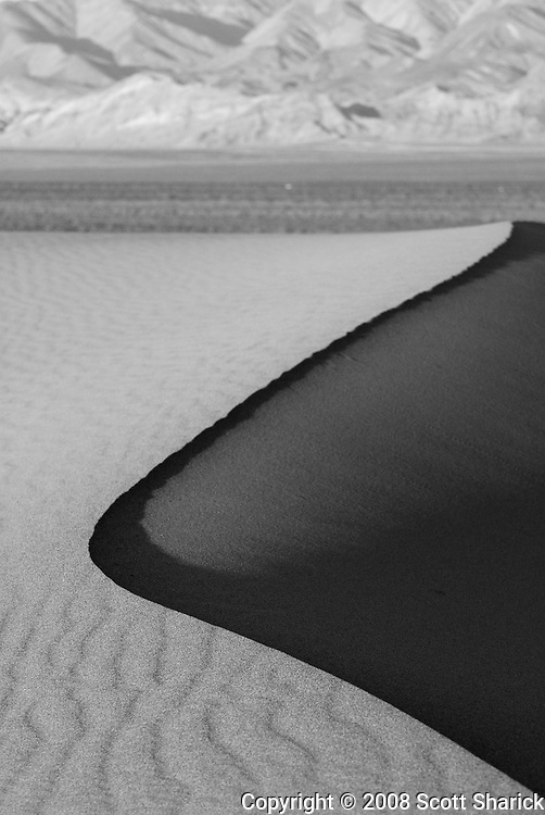 The sun lights up on side of a sand dune in this black and white image of a sand dune in Death Valley National Park.