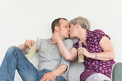 Mature couple kissing each other with drink bottle