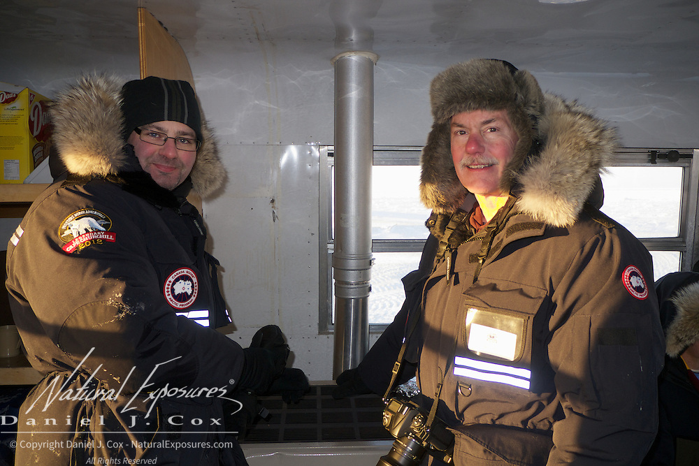 David Erdman and Daniel Smith warm their hands over a Tundra Buggy's propane stove while viewing polar bears at Cape Churchill, Hudson Bay, Manitoba.