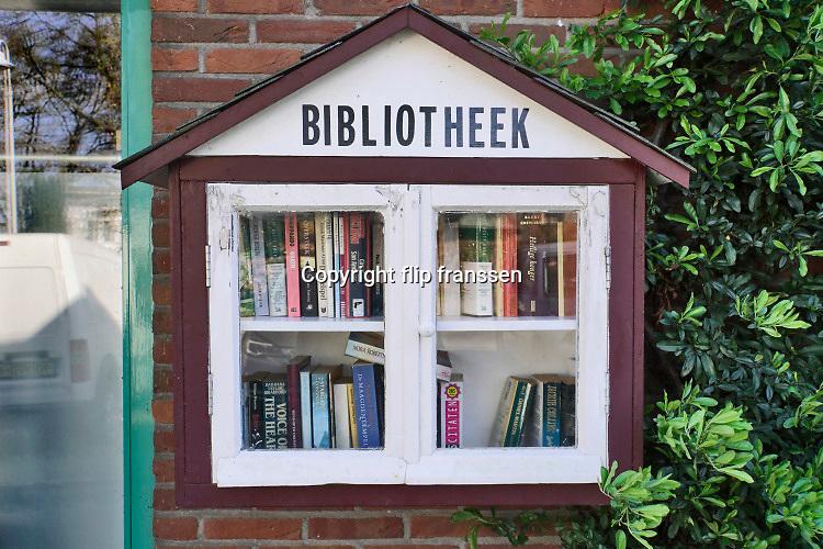 Nederland, Beek, 13-4-2020  Aan de gevel van een huis hangt een kastje met daarin boeken die je gratis mag lenen, meenemen, om te lezen . Foto: Flip Franssen