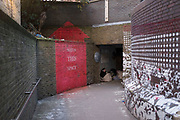 Homeless woman sat under cover at an underpass in the City of London, UK. Sitting huddled and wrapped up from the cold with her bags of belongings. A red sign painted on the wall in the shape of an arrow reads Watch This Space.