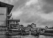 Saint-Laurent du Maroni, Guyane, 2015.<br /> <br /> Quartier du bac international, point de ralliement des taxis collectifs ou privés, légaux ou pas. Passage de marchandises en provenance  d'Albina, sur la rive surinamaise du fleuve.<br /> A Saint-Laurent, on prend la pirogue pour aller faire ses courses au Suriname. Pas besoin de visas pour se rendre à Albina  de l'autre côté du fleuve.<br /> <br /> Sous-préfecture, Saint-Laurent du Maroni est la deuxième plus grande ville de Guyane, située près de l'embouchure du Maroni à 253 km à l'ouest de Cayenne, face à la ville surinamaise d'Albina. La première activité de type industriel de Saint-Laurent est liée au commerce de l'or entre 1880 et 1888, mais la ville reste célèbre pour être devenue l'implantation principale du bagne en 1880, lorsqu'elle devient commune pénitentiaire. Aujourd'hui, Saint-Laurent est surtout perçue comme la porte d'entrée du Maroni sur le littoral.<br /> <br /> L'économie formelle de Saint-Laurent, prédominée par la fonction publique, est marquée par un taux de chômage qui touche près de la moitié des actifs et les résidents en situation administrative illégale représentent près du quart de la population. Un secteur économique « informel » et très dynamique s'y est développé, naturellement tourné vers le fleuve.