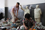 Stall owners with famous waving Mao Zedong statues for sale in the indoor antique market in Yu Yuan Garden, downtown Shanghai, China. The pots and ceramics being sold by this family business on the top floor of the market are not genuine antiques. Many are fakes, which are sold to the more gullible tourists. Genuine antiques can be bought but the prices reflect their age considerably. Mao Zedong, commonly known as Chairman Mao, was a Chinese communist revolutionary who became the founding father of the Peoples Republic of China, which he ruled as the Chairman of the Communist Party.