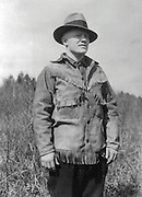 Gordon MacQuarrie wearing a fringed buckskin jacket, at Little Bass Lake, WI, 1928.