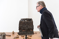 """© Licensed to London News Pictures. 17/04/2018. LONDON, UK. A visitor views """"Boothia Felix"""", 1958/82, a metal tripod, terracotta shards, earth and rosemary roots, at the preview of """"Joseph Beuys: Utopia at the Stag Monuments"""", at the Galerie Thaddaeus Ropac in Dover Street.  The retrospective is the most important UK exhibition of Beuys' work in over a decade, presenting major sculptures and rarely seen works from 1947 to 1985, and runs from 18 April to 16 June.  Photo credit: Stephen Chung/LNP"""