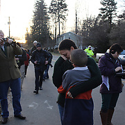 A women and boy embrace after visiting the shrine created under the school sign in Sandy Hook after yesterday's shootings at Sandy Hook Elementary School, Newtown, Connecticut, USA. 15th December 2012. Photo Tim Clayton