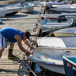 Jackson Feener, sternman on the lobster boat, 'Redeemed', tying up a skiff at the Spruce Head Fisherman's Co-op in South Thomaston, Maine.