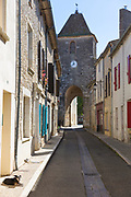 13th Century medieval gateway clock tower, dog in empty street in ancient bastide fortified town of Duras in Aquitaine, France