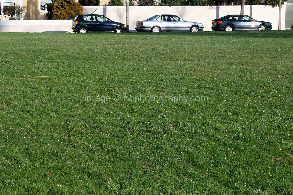 Three cars parked in a row in front of green field in suburban area of Dublin Ireland