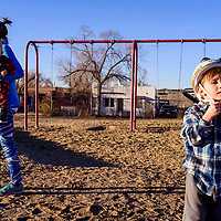 John Marie Mason, right, straps on his bike helmet as his mother Rachel Mason carries his little brother Conor Mason across the playground at Roosevelt Elementary School in Gallup Thursday.