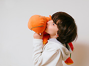 Young boy of seven plays with a large stuffed doll
