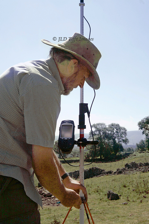 Archaeologist Dr. Roger Martlew setting up a survey at Chapel House Wood, Upper Wharfedale, Yorkshire.  Three quarter view in profile with instrument, moor visible beyond.  Slight lens flare visible over the subject's ear.