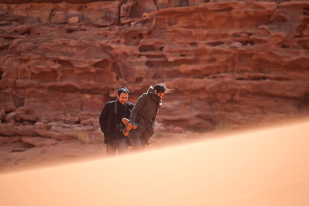 Tourists hike up a sand dune in high winds in Wadi Rum, Jordan.