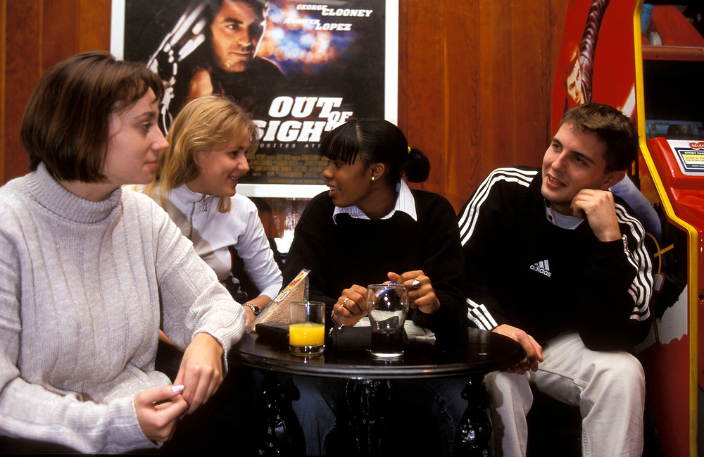 A group of friends  chatting over a drink in the student union bar,