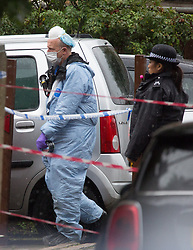 © Licensed to London News Pictures.  02/10/2021. London, UK. A forensic officer gathers evidence while police guard a crime scene after the 35-year-old man been shot to death after leaving the house party in Croydon, south London. Police were called to reports of a man being wounded shortly before 5am.  Photo credit: Marcin Nowak/LNP