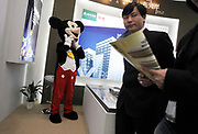 A man puts on his Mickey Mouse costume at a real estate fair in Shanghai, China on 15 March, 2009.  For the past decade, Shanghai has underwent the largest reconstruction in recorded history, over 20 million square meters of land, approximately a third of Manhattan, were developed between year 200 and 2005 alone. Despite that however, housing prices have seen a rapid increase, putting the prospect of owning a decent sized home out of the reach of ordinary Chinese citizens, especially middle to low income families.