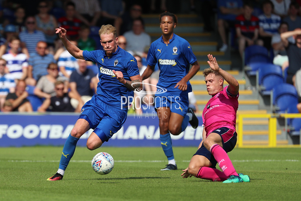 Wimbledon midfielder Mitchell (Mitch) Pinnock (11) battles for possession with Queens Park Rangers defender Jake Bidwell (3) during the Pre-Season Friendly match between AFC Wimbledon and Queens Park Rangers at the Cherry Red Records Stadium, Kingston, England on 14 July 2018. Picture by Matthew Redman.