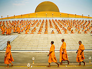 """22 FEBRUARY 2016 - KHLONG LUANG, PATHUM THANI, THAILAND: Monk walk into the chedi while other monks sit around the chedi during Makha Bucha Day at Wat Phra Dhammakaya.  Makha Bucha Day is a public holiday in Cambodia, Laos, Myanmar and Thailand. Many people go to the temple to perform merit-making activities on Makha Bucha Day, which marks four important events in Buddhism: 1,250 disciples came to see the Buddha without being summoned, all of them were Arhantas, Enlightened Ones, and all were ordained by the Buddha himself. The Buddha gave those Arhantas the principles of Buddhism, called """"The ovadhapatimokha"""". Those principles are:  1) To cease from all evil, 2) To do what is good, 3) To cleanse one's mind. The Buddha delivered an important sermon on that day which laid down the principles of the Buddhist teachings. In Thailand, this teaching has been dubbed the """"Heart of Buddhism."""" Wat Phra Dhammakaya is the center of the Dhammakaya Movement, a Buddhist sect founded in the 1970s and led by Phra Dhammachayo. The temple is famous for the design of its chedi, which some have likened to a flying saucer or UFO.         PHOTO BY JACK KURTZ"""