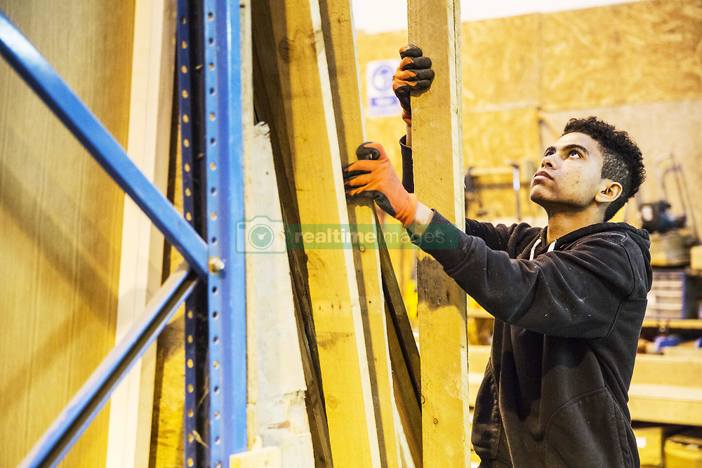 February 15, 2018 - Young man wearing work gloves standing next to a stack of wooden planks in a warehouse, holding plank, looking up. (Credit Image: © Mint Images via ZUMA Wire)