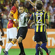 Galatasaray's player Johan Elmander and Fenerbahce's player Egemen Korkmaz are speaking with refeere Cuneyt Cakir about an objection on the match  their Turkish Super Cup 2012 soccer derby match Galatasaray between Fenerbahce at the Kazim Karabekir stadium in Erzurum Turkey on Sunday, 12 August 2012. Photo by TURKPIX