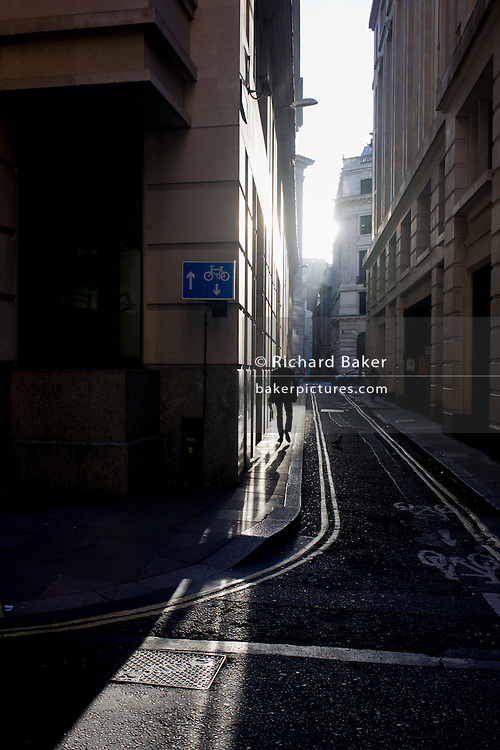 A lone man walks through winter sunlight near the corner of Lombard Street and Abchurch Lane, EC4, in the City of London.