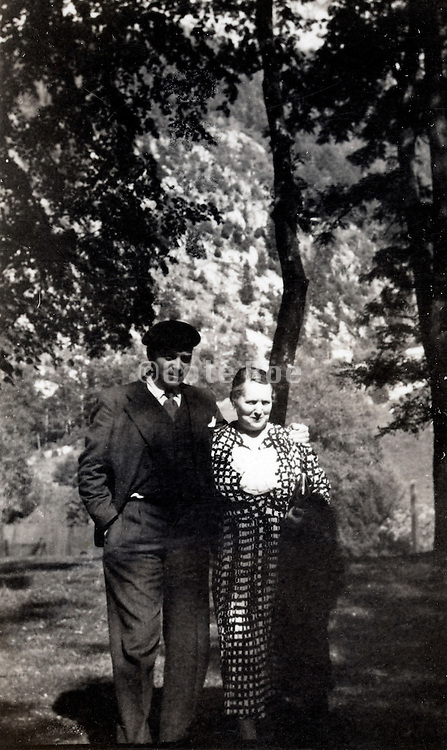 two adult people posing in the outdoors