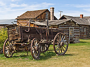 """A wagon with iron-bound wooden wheels stands outside late 1800s wooden buildings preserved at the outdoor history museum of Nevada City, Montana, USA. Nevada City was a booming placer gold mining camp from 1863-1876, but quickly declined into a virtual ghost town. This fascinating town inspires you to imagination what life must have been like in early Montana when gold was discovered at nearby Alder Gulch. More than 90 buildings from across Montana have been gathered for preservation at Nevada City, mostly owned by the people of the State of Montana, and managed by the Montana Heritage Commission. In 2001, the excellent PBS television series """"Frontier House"""" used one of the buildings and its furnishings to train families in re-creating pioneer life. A miner's court trial and hanging of George Ives in the main street of Nevada City was the catalyst for forming the Vigilantes, a group of citizens famous for taking justice into their own hands in 1863-1864. Directions: go 27 miles southeast of Twin Bridges, Montana on Highway 287."""