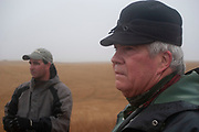Experienced hunter Byron Grubb with his son Eric out on the North Dakota prarie grasslands shooting upland game birds such as grouse near Minot, North Dakota, United States. Byron and Eric have been shooting for most of their lives and put considerable efforts into his hunting, efforts which reward them with wild game meats, none of which is wasted. This cold wet morning is not ideal for this type of shooting as the birds tend to sit tight in the undergrowth. The hunters on occasion nearly tread on the birds before they will take flight.