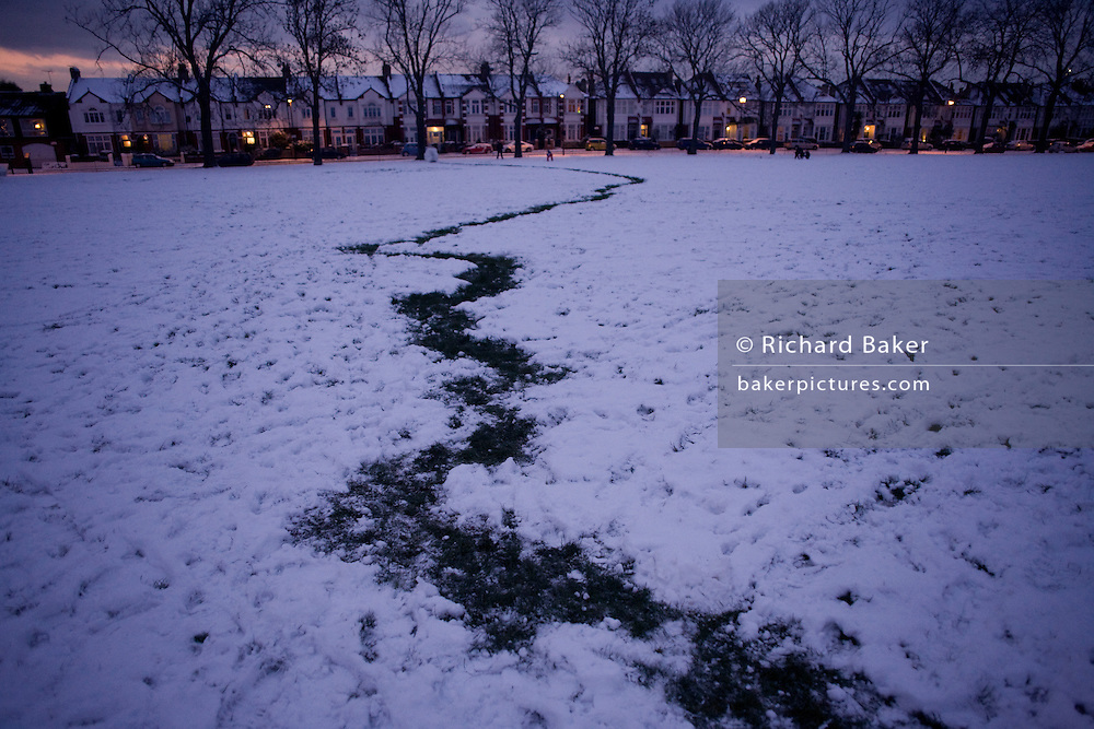 London homes and trail of bare grass after snowman-building in a few inches of snow during early 2010 snows that gripped the UK.