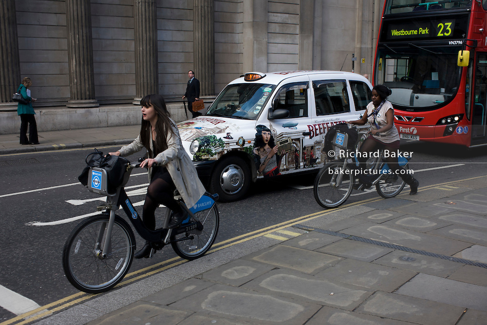 Young women nervously cycle over a road junction riding Boris bikes outside the Bank of England in the City of London.