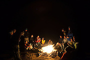 Students on a geology field trip with the University of Colorado gather around a bonfire at night at their campsite in the San Rafael Swell, Utah.