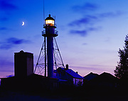 Crescent moon and Whitefish Point Light Station at dusk, light tower dating from 1861-62 and fog signal building dating from 1936, Lake Superion shore, Upper Peninsula of Michigan.