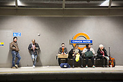 People waiting for a London Overground train on the platform at Canada Water station. London, UK.