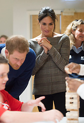 Prince Harry and Meghan Markle watch a game of Jenga during a visit to Star Hub in Tremorfa.