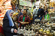 Shopper buying coffee pot and cups in Misir Carsisi Egyptian Bazaar food and spice market in Istanbul, Turkey