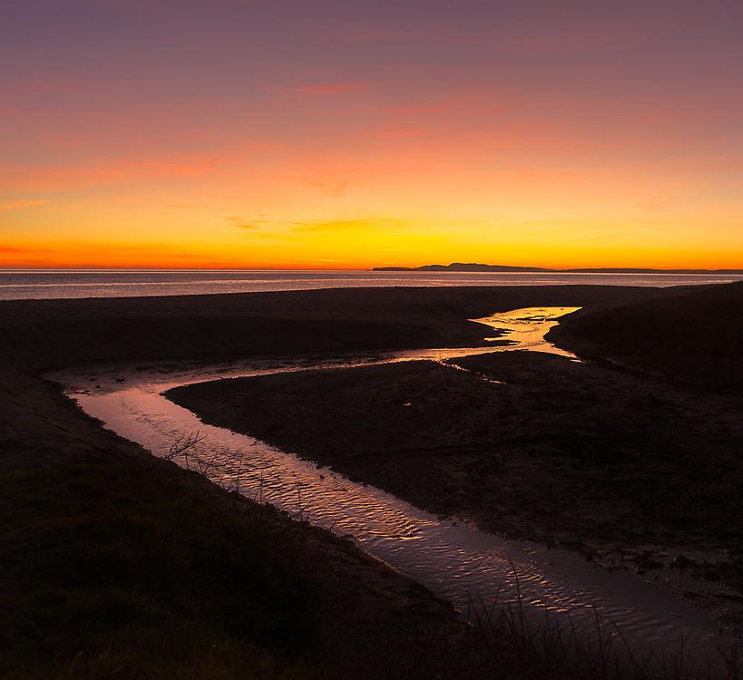 A seasonal creek drains toward the Pacific as the sun sets over Drake's Bay.